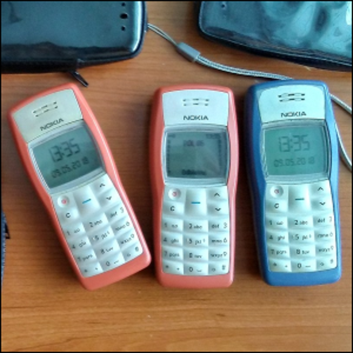 Three Nokia 1100 phones laying on a table.