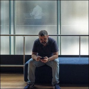 A man checking his phone after feeling like he missed a notification.