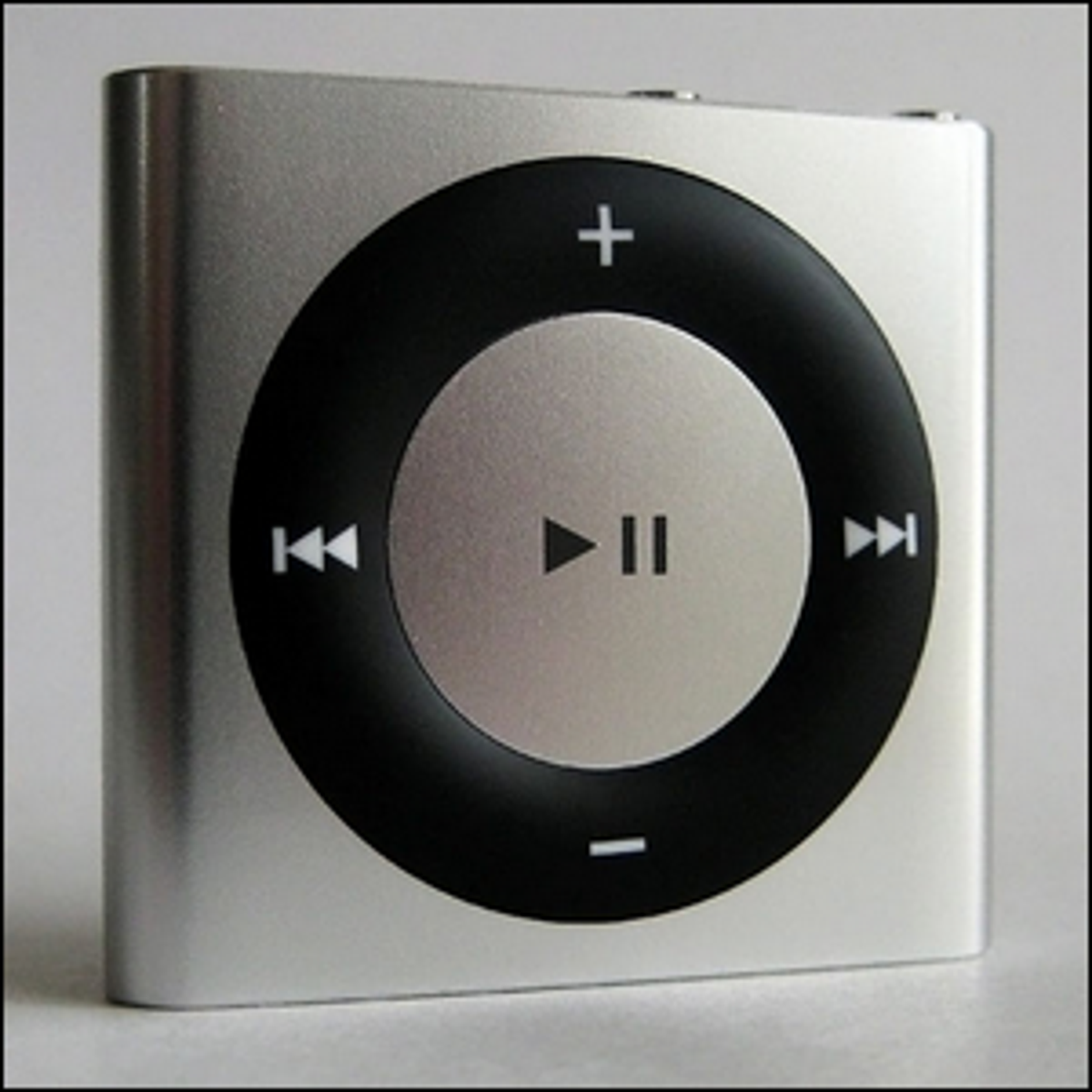 A silver iPod Shuffle 4G with the pause symbol clearly seen in the middle of the central control button.