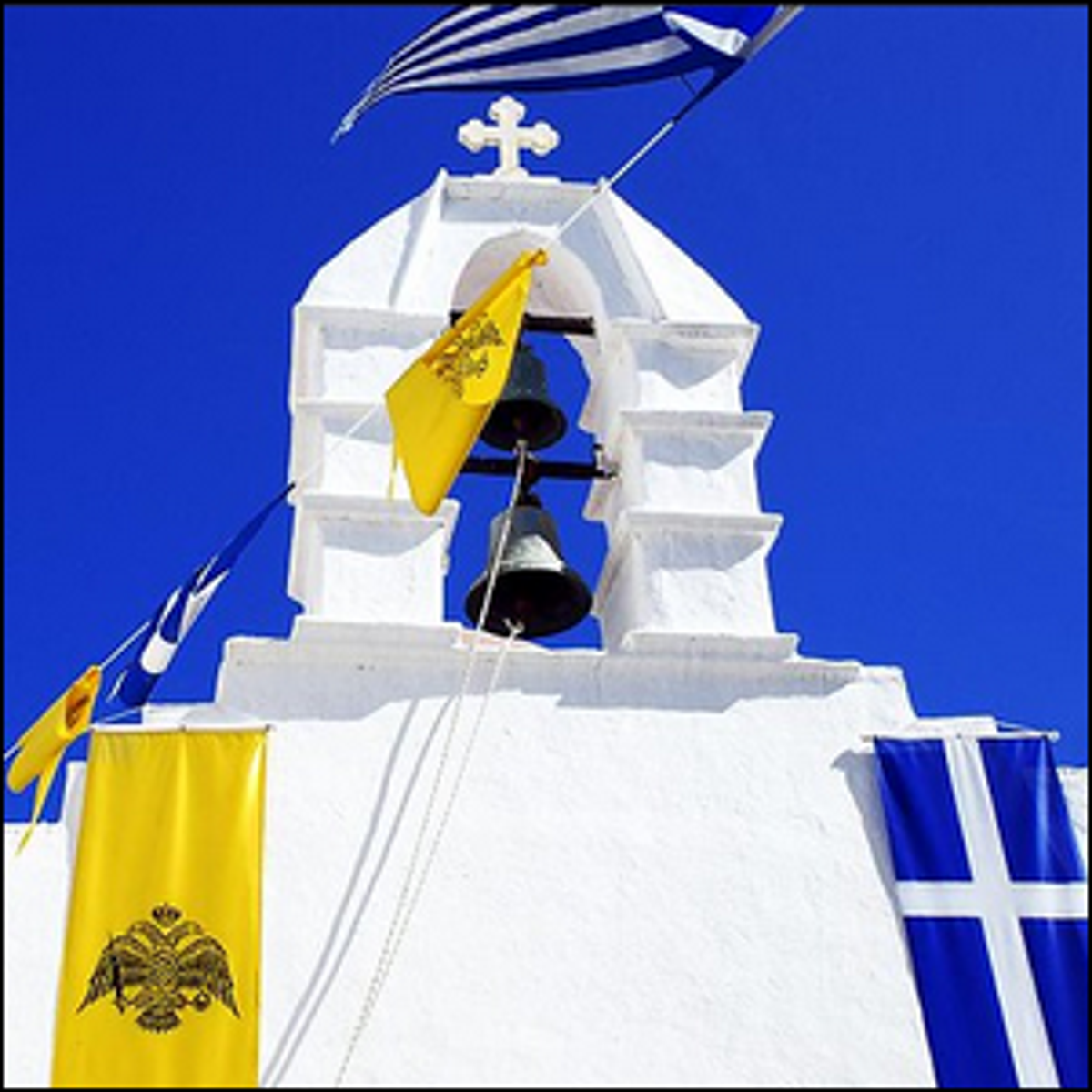 A beautiful white building with a Greek flag flying from the top.