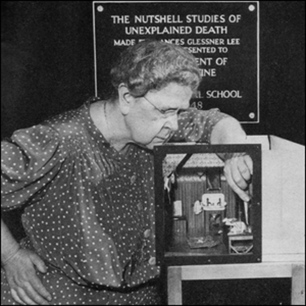 A photo of Frances Glessner Lee showing off one of her miniature dollhouse dioramas. (S.E.P. - February 10, 1949)