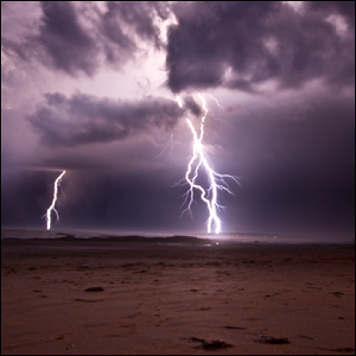 Lightning striking a sandy beach.