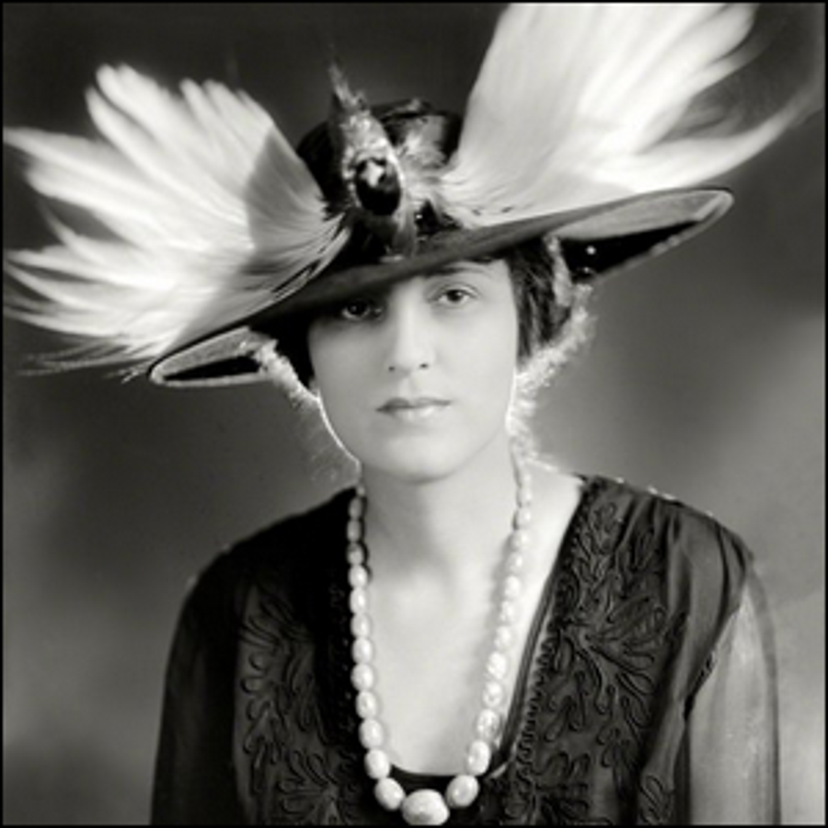 A photograph of an early 20th century woman wearing an elaborate bird hat.