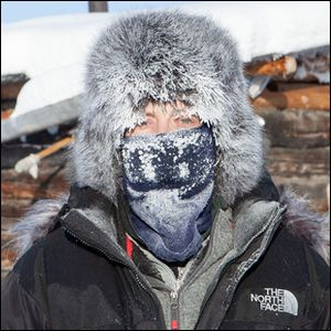 A picture of an individual standing in the coldest permanently inhabited place on Earth.