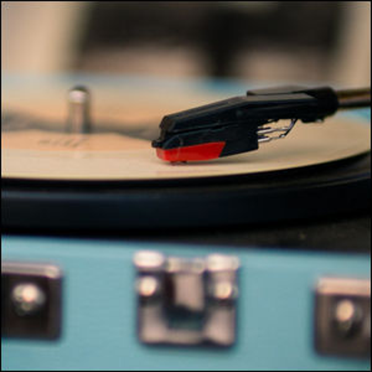 A record stylus tracing the groove on a vinyl record.