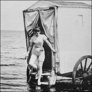 A woman stepping out of a bathing machine and into the ocean.