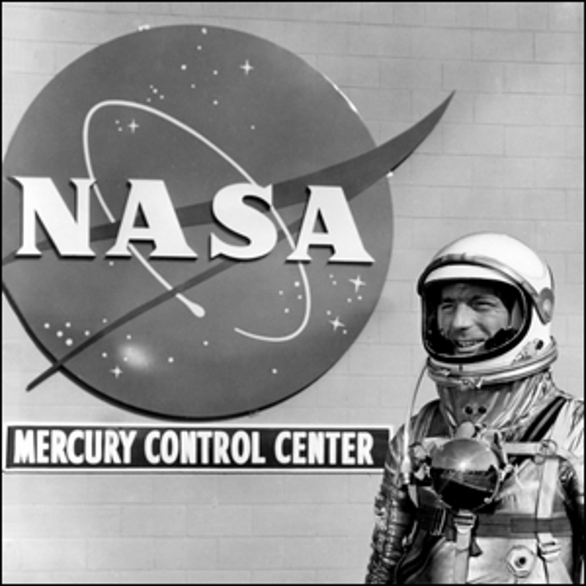 Mercury astronaut Scott Carpenter standing in front of the NASA insignia at Cape Canaveral.