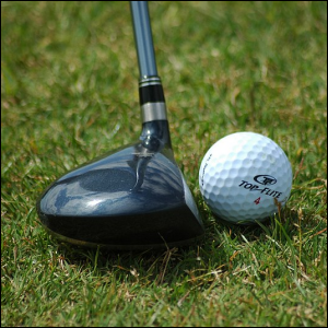Photo of a golf club positioned to hit a golf ball.