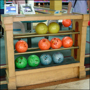 A wooden storage rack with bowling balls in it.