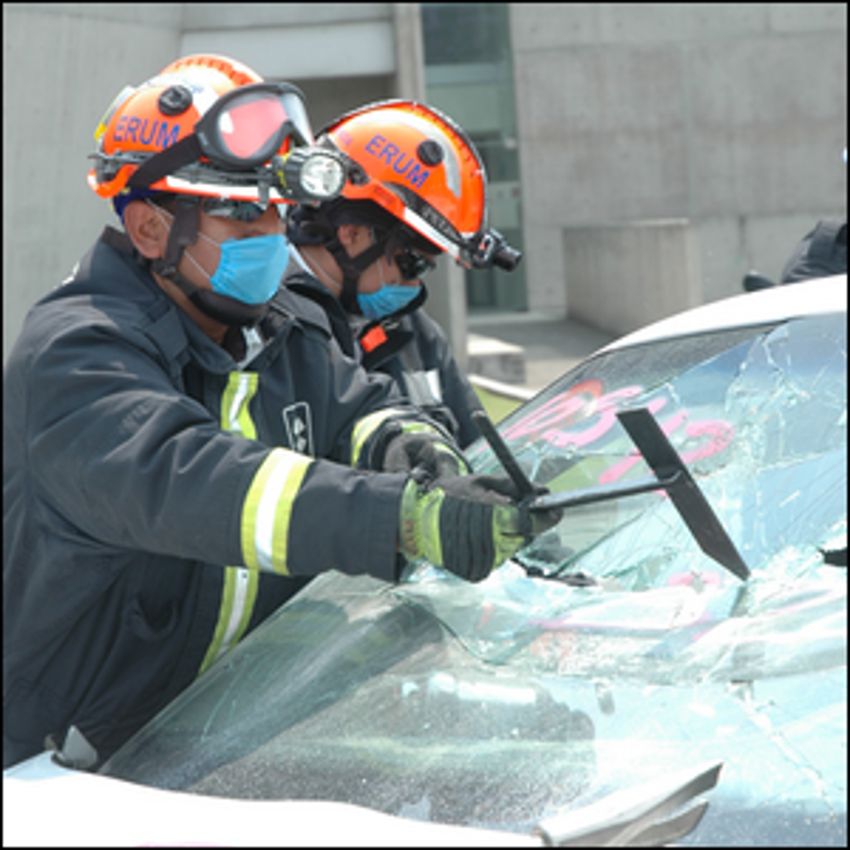 Firefighters breaking through a laminated windshield.
