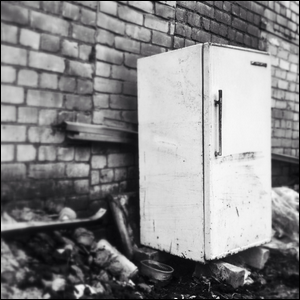 An old, abandoned refrigerator in an alley.