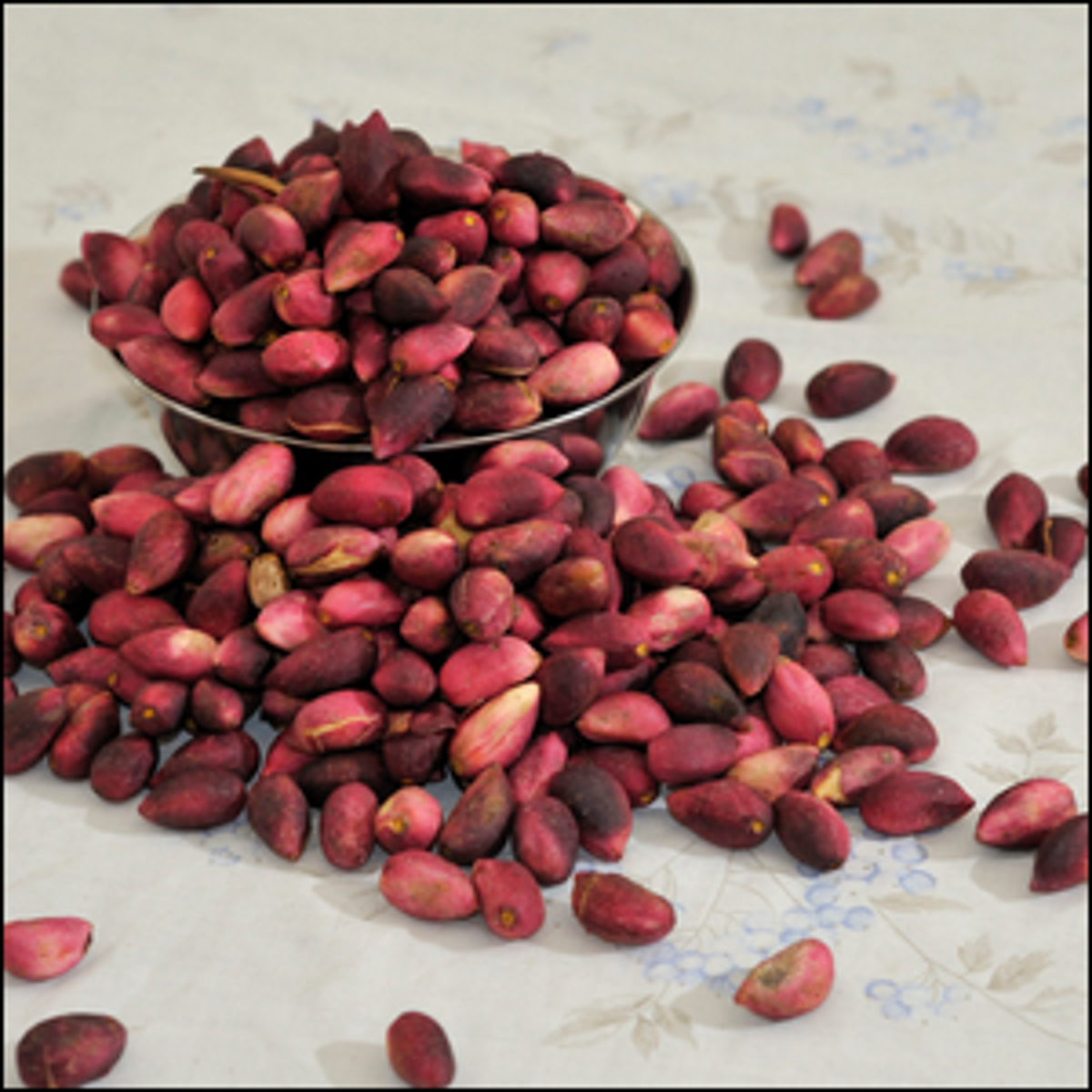 An overflowing bowl of raw pistachio nuts.