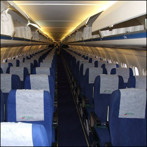 A photo of airplane seats with antimacassars on them.