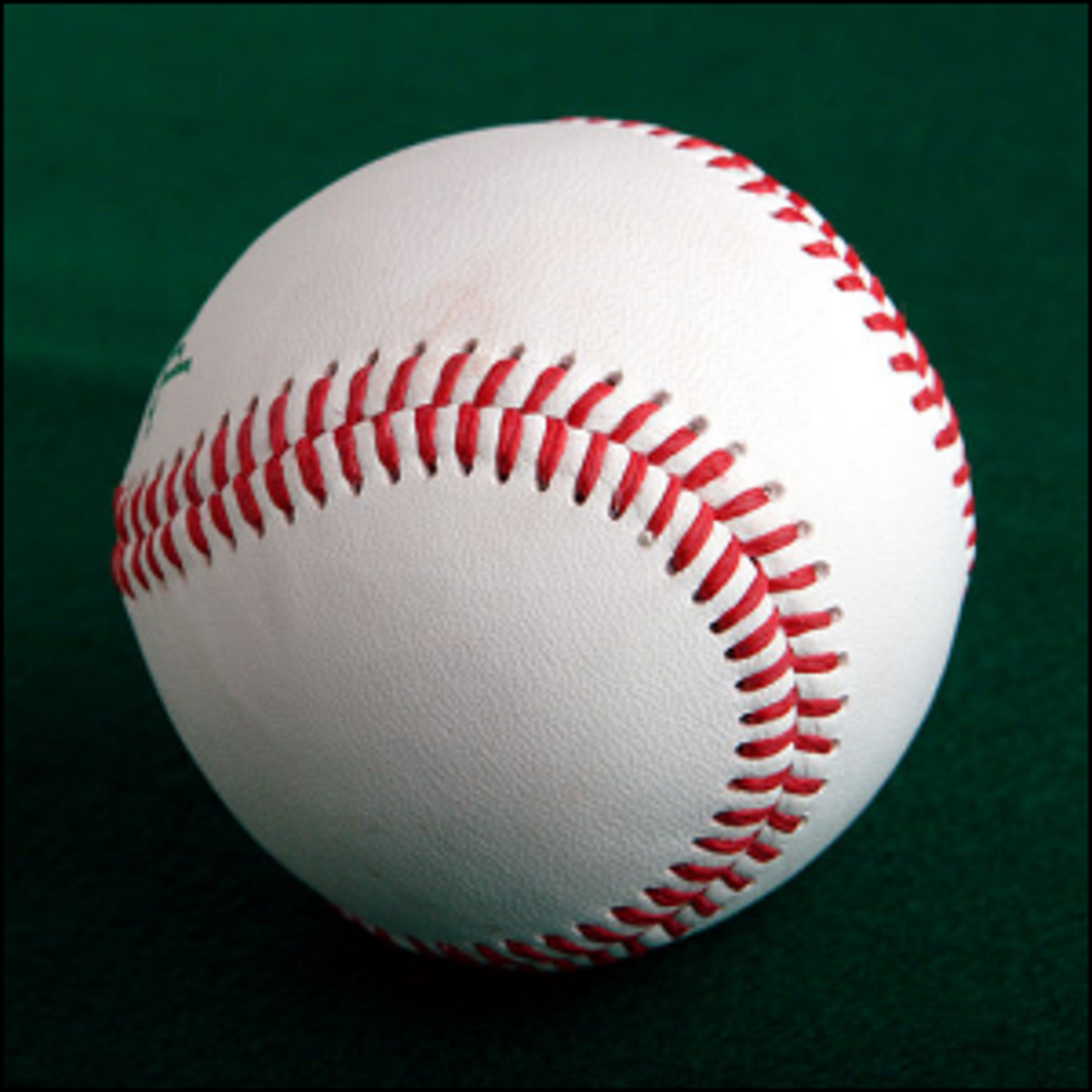 A new baseball sitting on a green cloth surface.