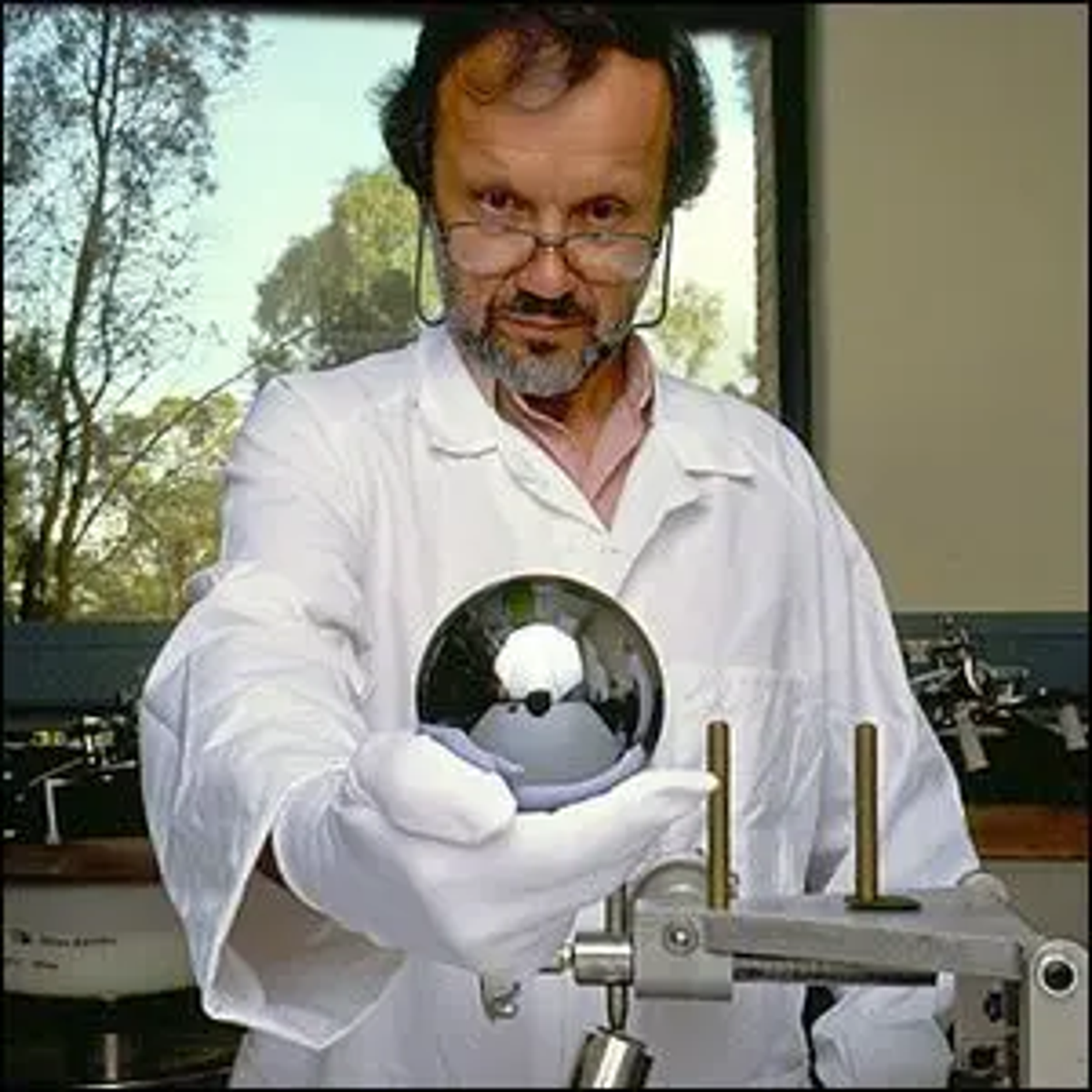 A one kilogram single-crystal silicon sphere being held by Master Optician Achim Leistner.