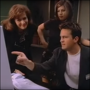 Jennifer Aniston and Matthew Perry sitting at Bill Gates' desk in the Windows 95 training video.