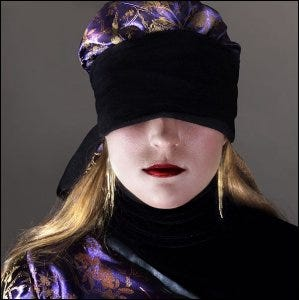 A woman who is currently blindfolded.