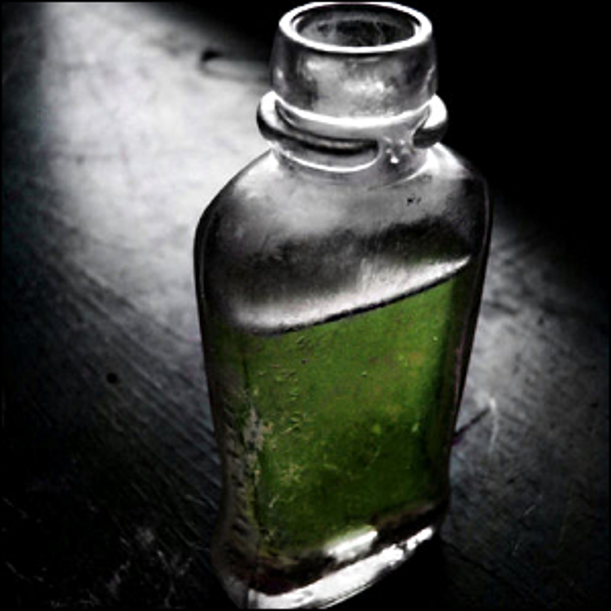 A small bottle with a green liquid inside.