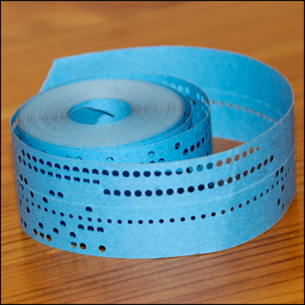 A roll of blue punched paper tape containing a computer program.