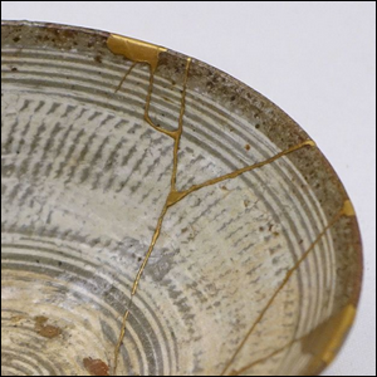 Repair work on a Mishima ware hakeme-type tea bowl with kintsugi gold lacquer, 16th century.