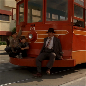 Private detective Eddie Valiant sitting on a Toontown trolley car.