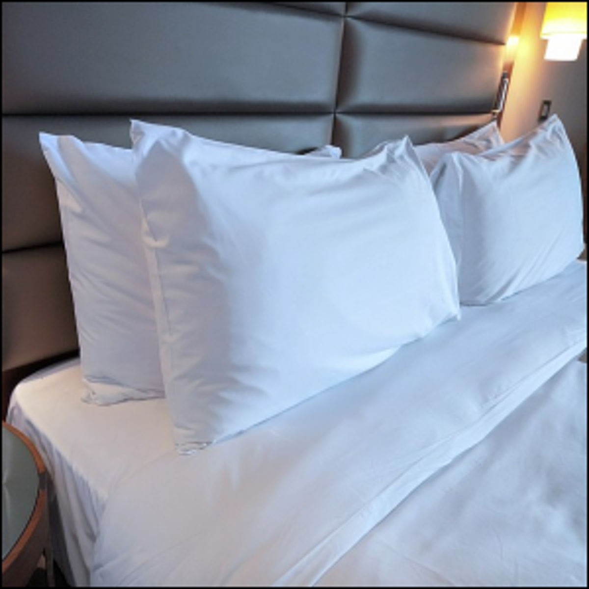 A set of four pillows on a hotel bed.