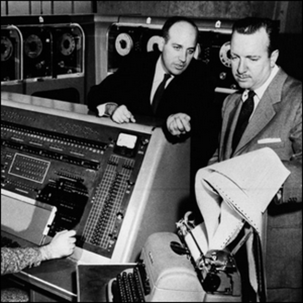 Walter Cronkite listening to Dr. J. Presper Eckert as he describes the functions of the UNIVAC I computer.