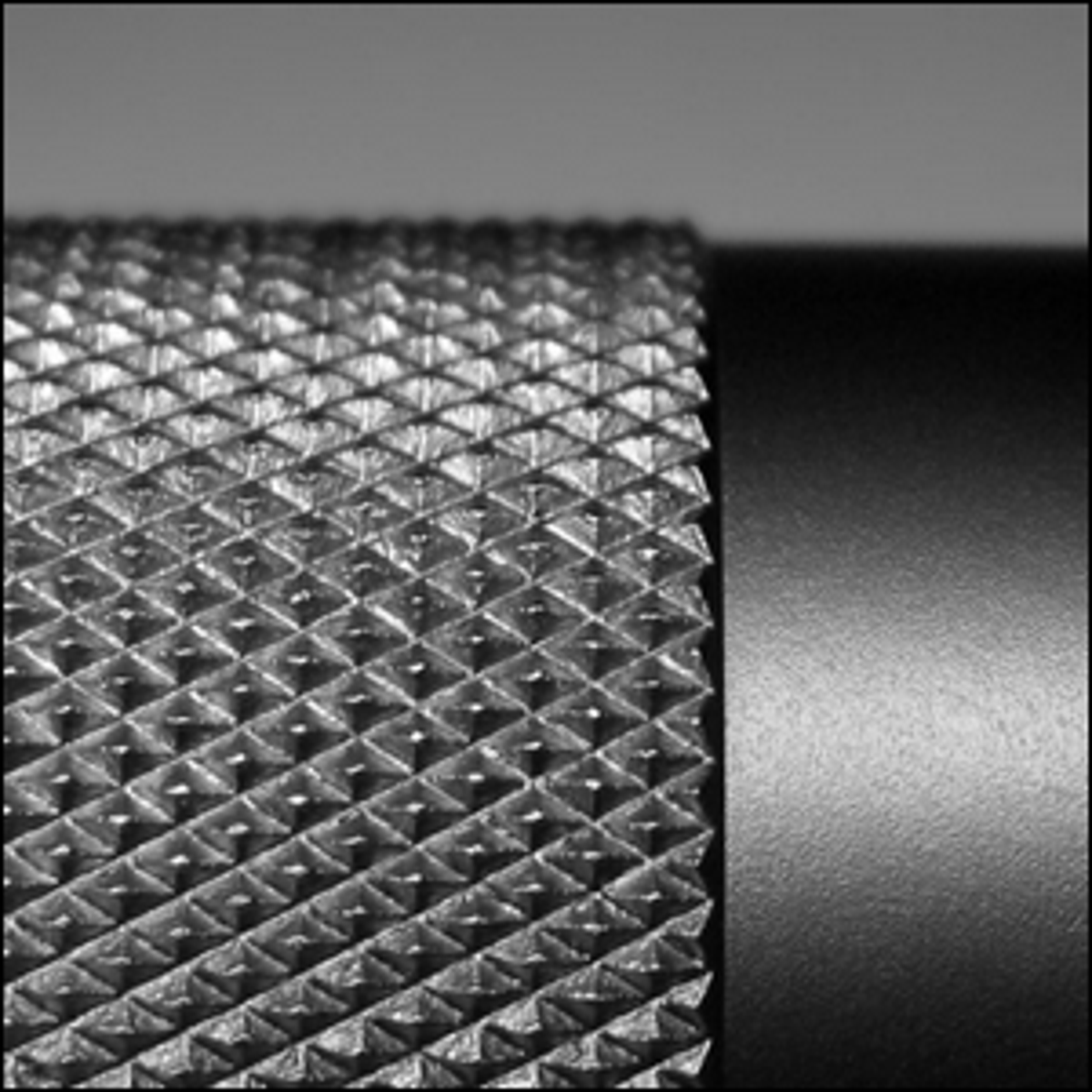 A close-up photo of diamond-pattern knurling on a cylindrical piece of metal.