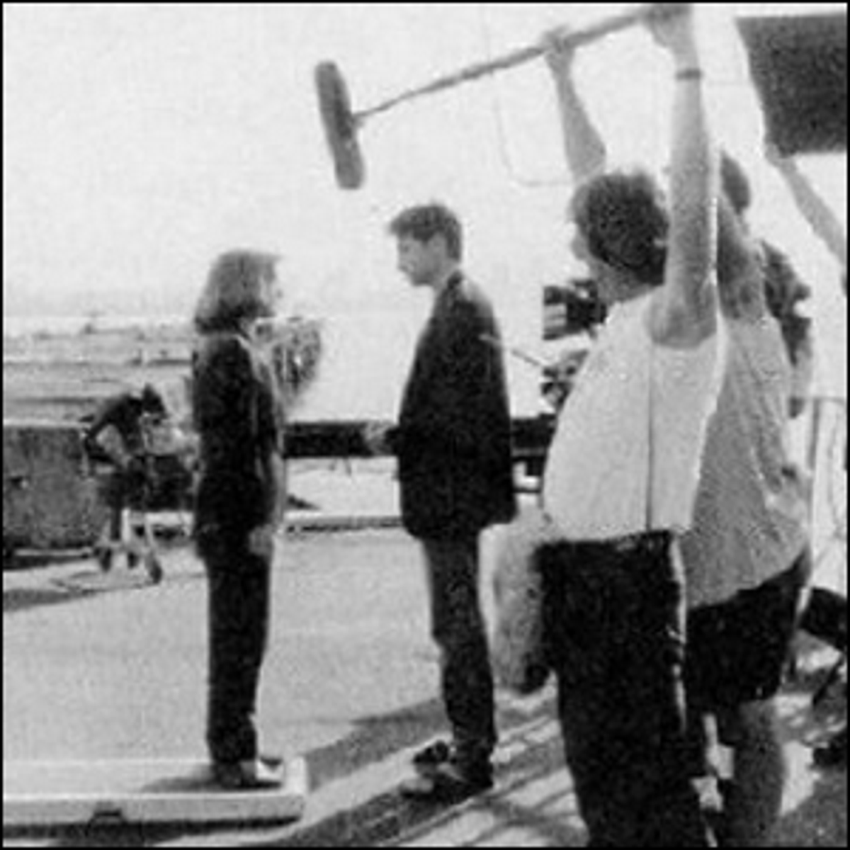 Actress Gillian Anderson standing on an apple box next to her co-star David Duchovny.