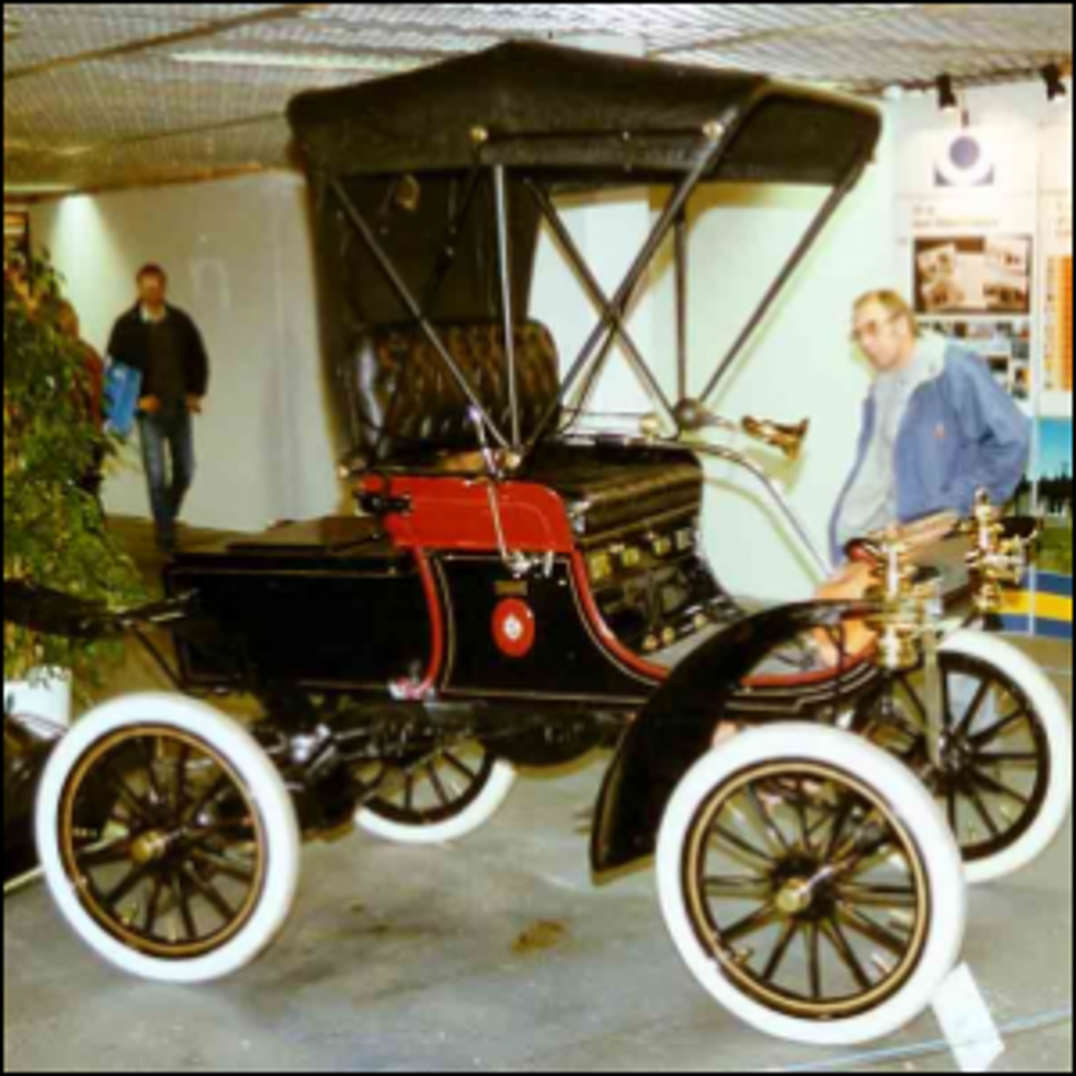 A 1904 Oldsmobile Model 6C Curved Dash Runabout with its top up.