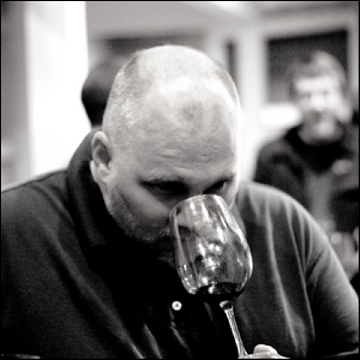 A man smelling the aroma and bouquet of wine in a glass as part of wine tasting.