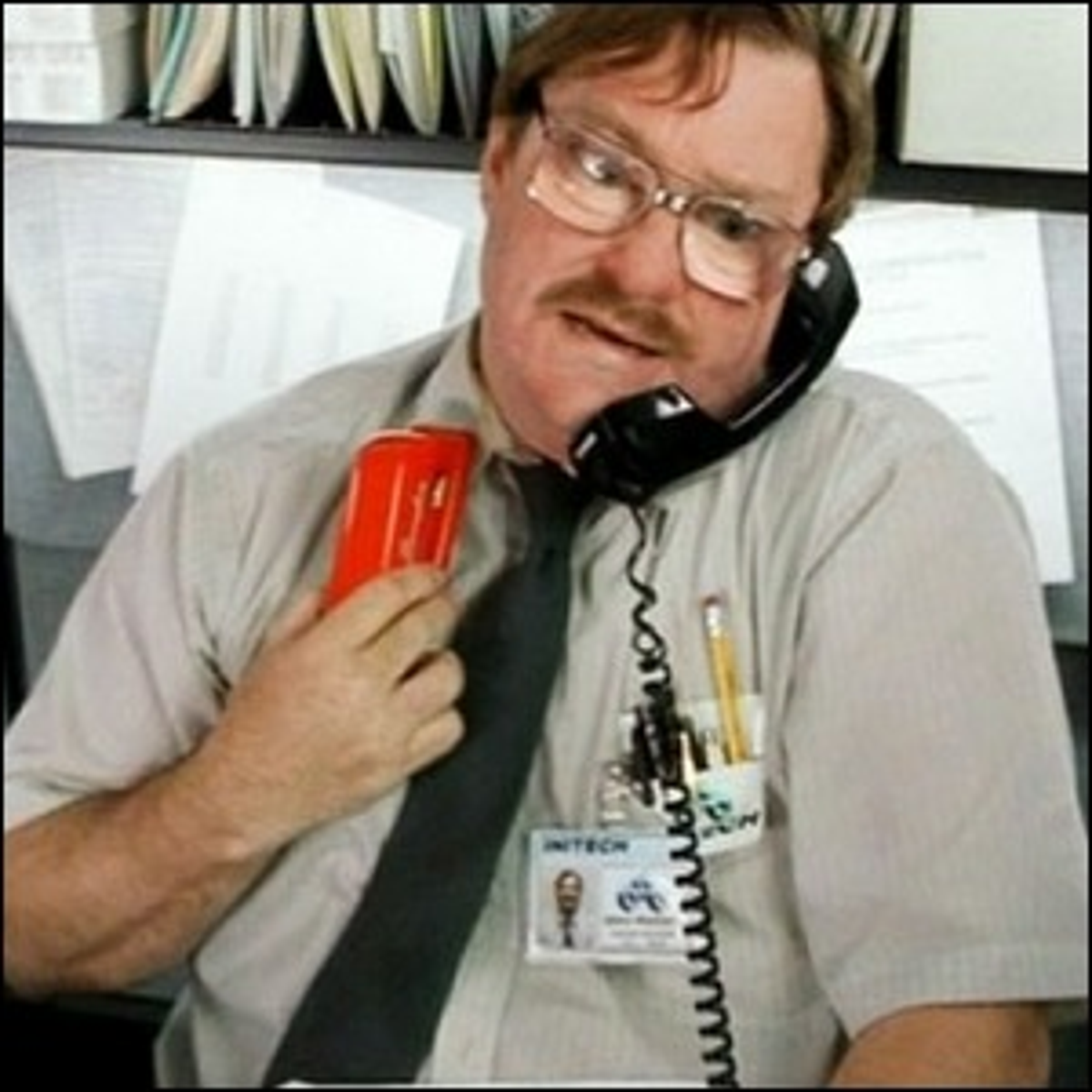 Milton, from the movie Office Space, holding his red stapler.