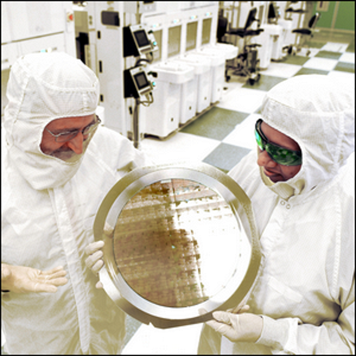 Engineers holding up a wafer of 7mm chips.