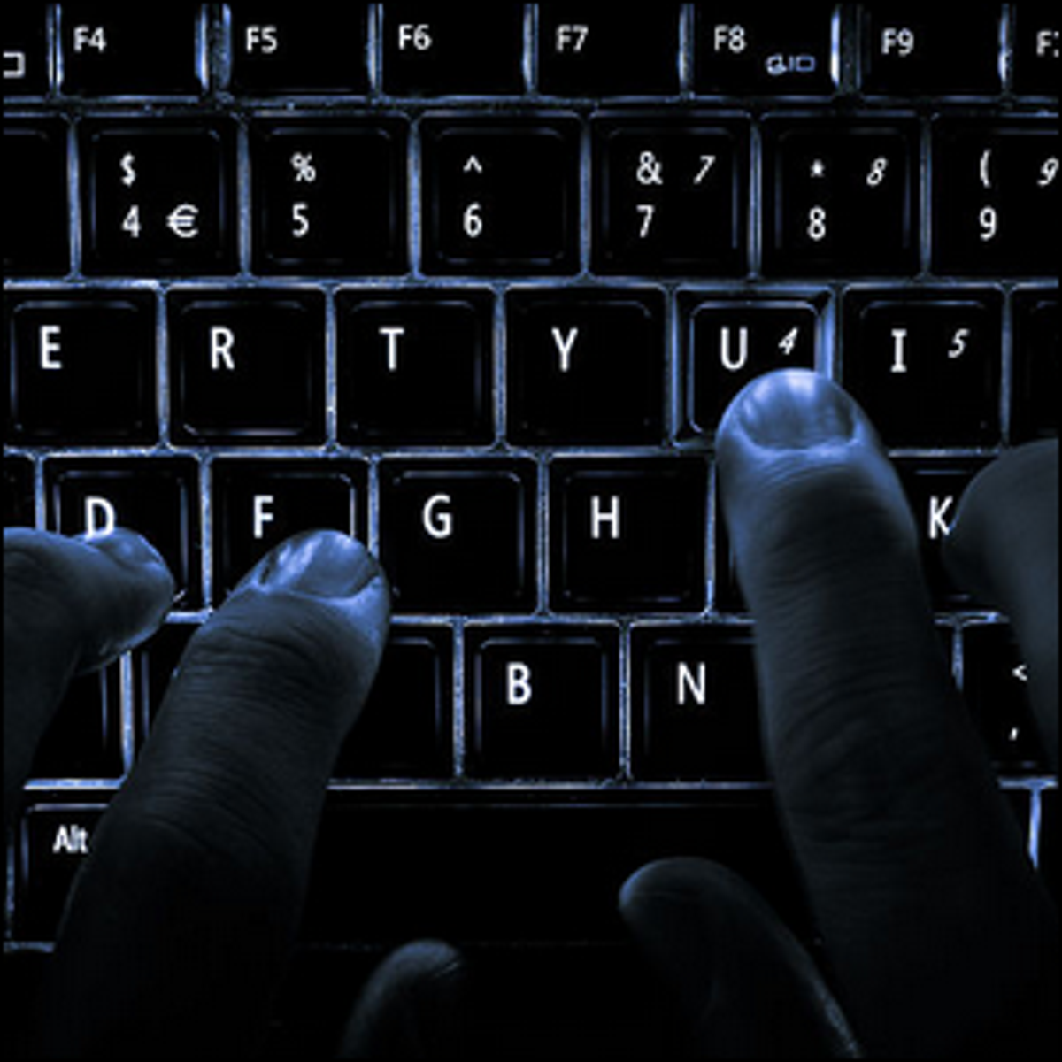 Fingers typing on a backlit keyboard.
