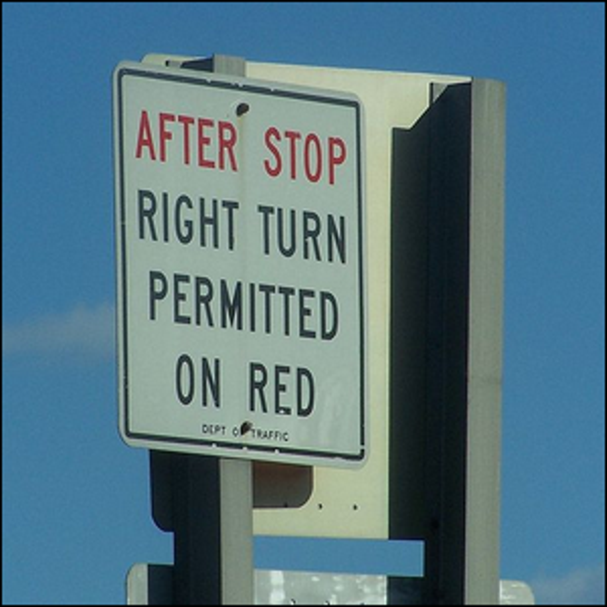 "An example of a right turn sign reading, ""After stop, right turn permitted on red."""