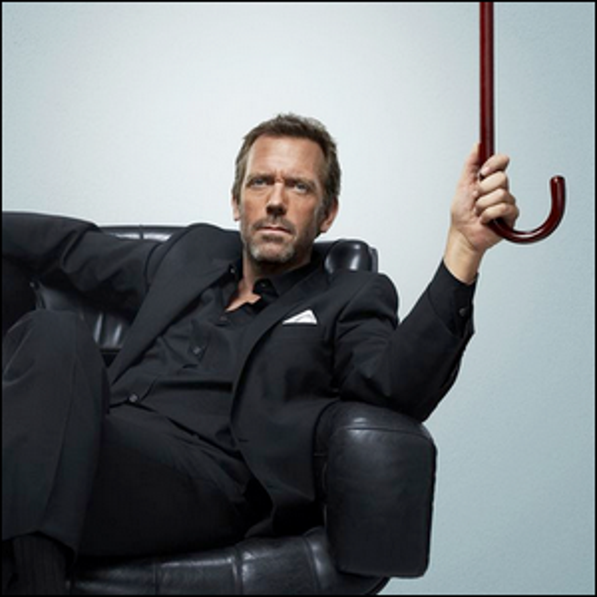 "Hugh Laurie sitting in a leather chair holding the cane used for his role in the TV show ""House""."