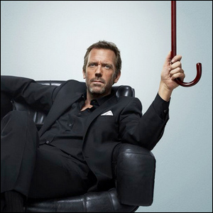 """Hugh Laurie sitting in a leather chair holding the cane used for his role in the TV show """"House""""."""