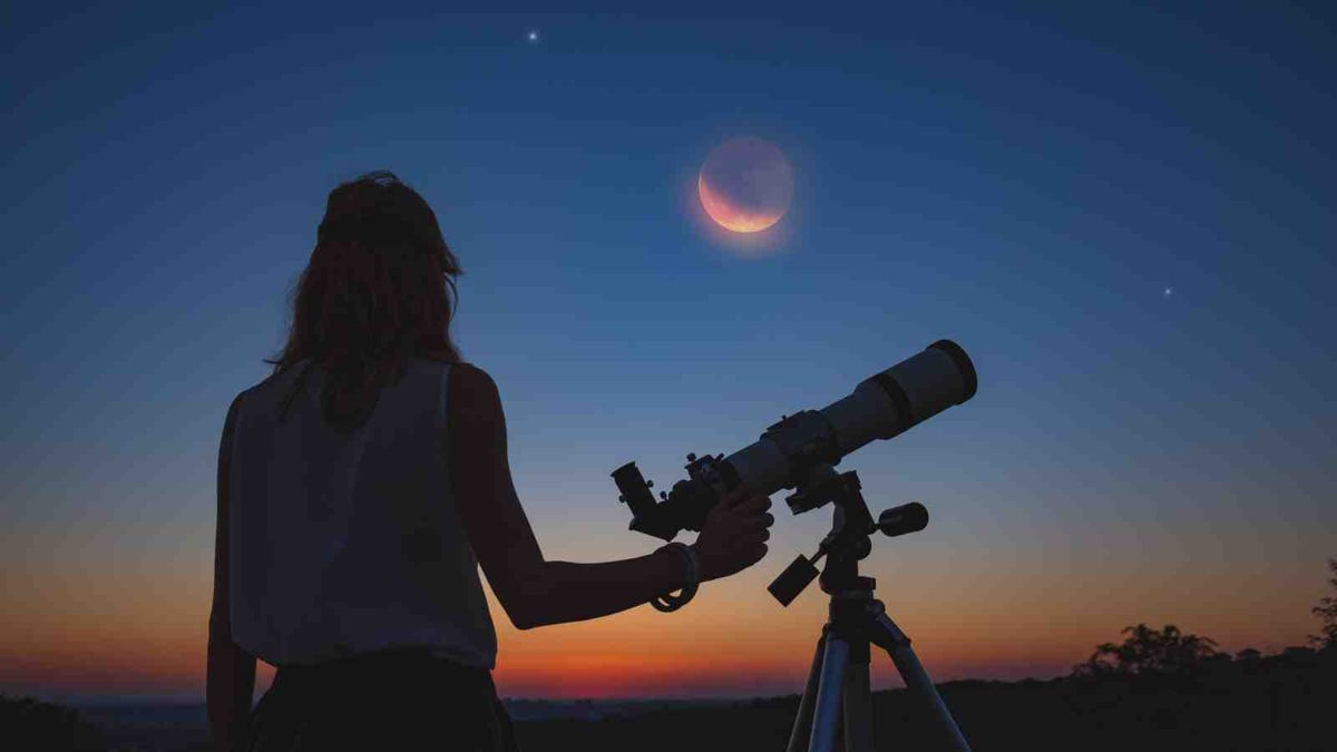 silhouette of woman looking at lunar eclipse