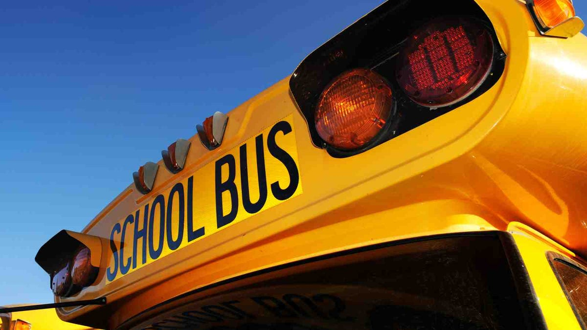 Close up photo of school bus on sunny day with clean blue background