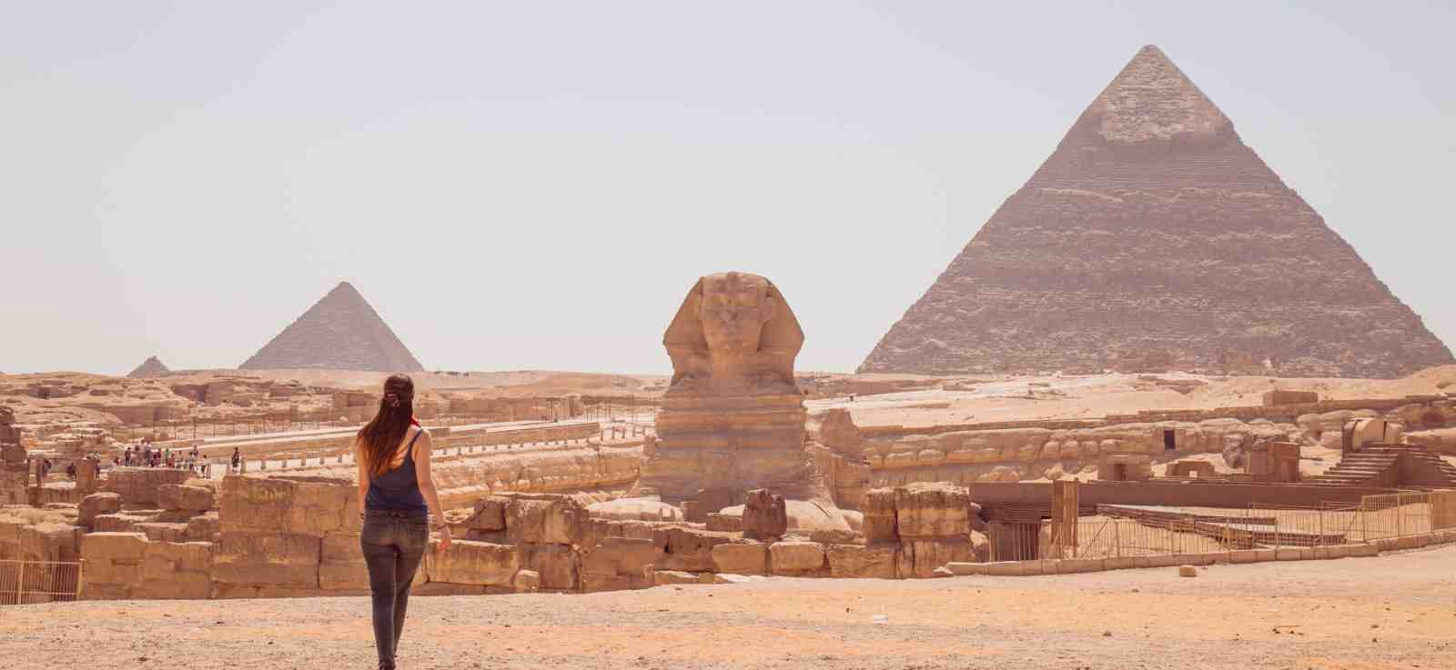 Young woman standing in front of the Great Sphinx of Giza with the Pyramids in the background