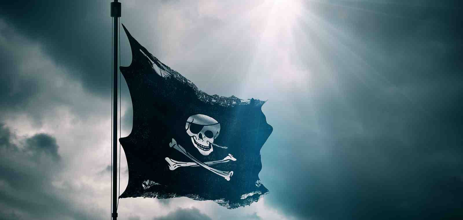 tattered skull and crossbones pirate flag against cloudy sky