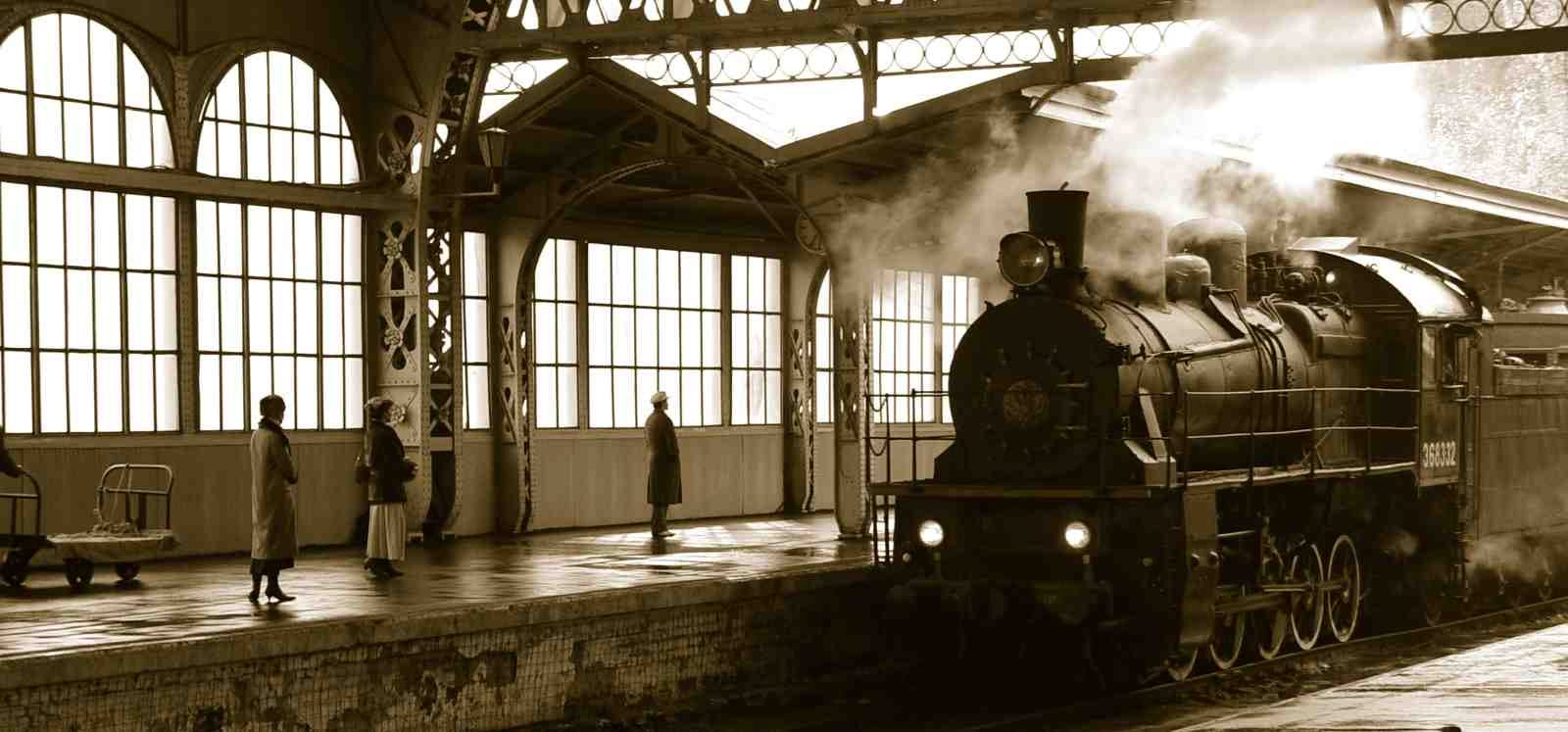old steam engine train pulling into station