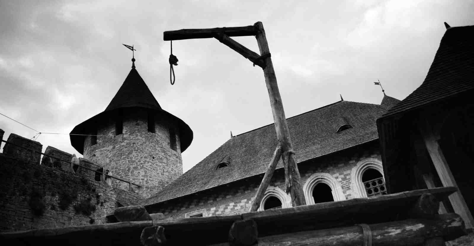 Medieval gallows on the background of a medieval castle