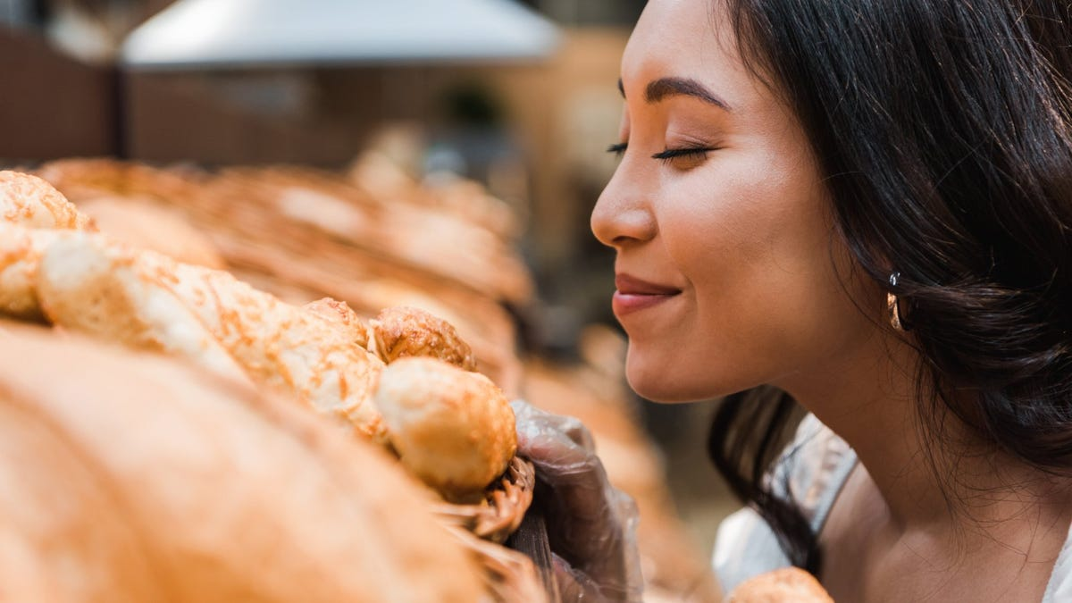 woman smiling while smelling bread in supermarket