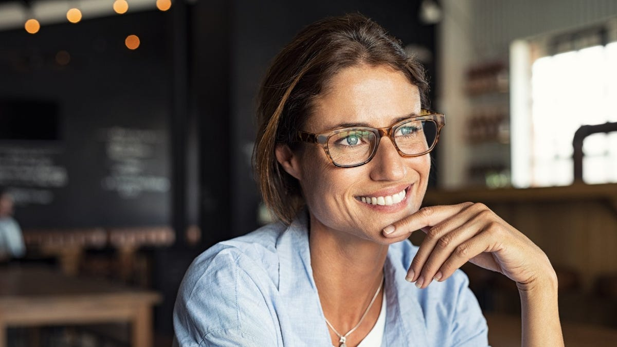 Woman sitting in cafe in thoughtful post with finger on chin
