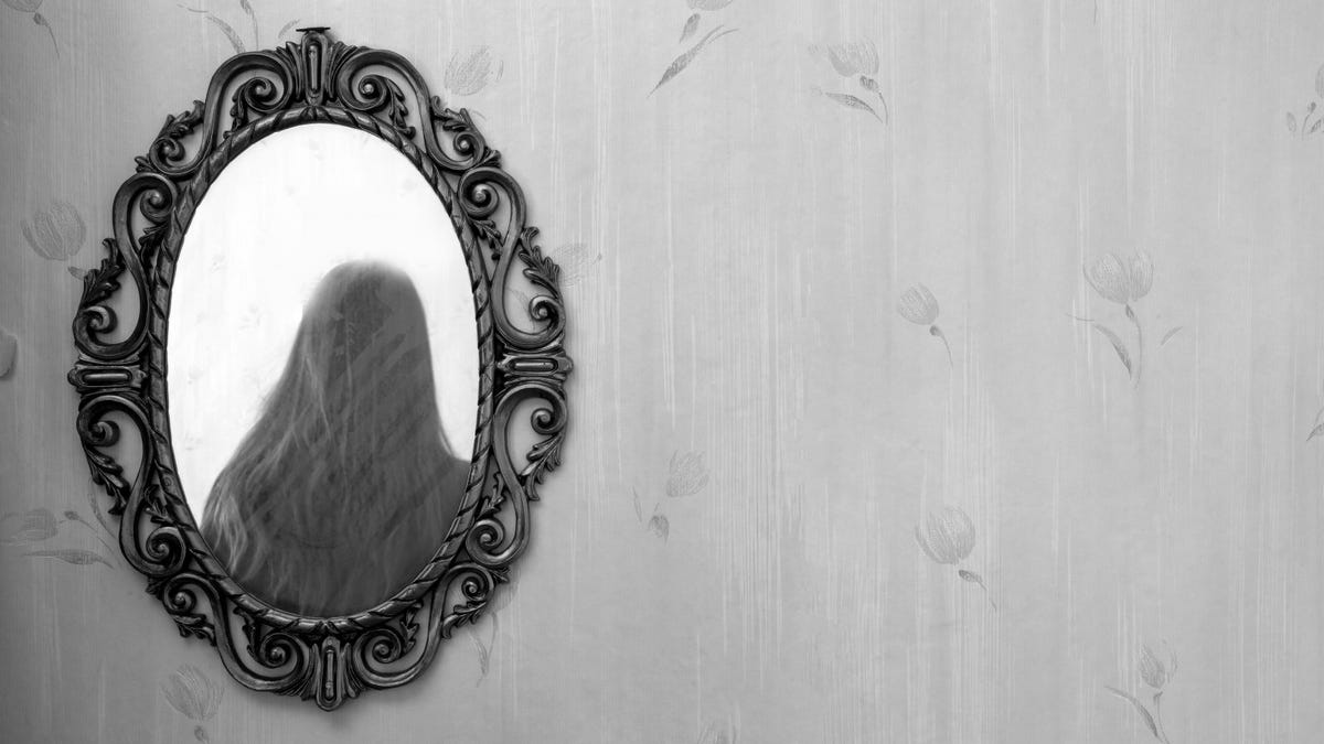 shadowy reflection of a woman in a antique golden mirror