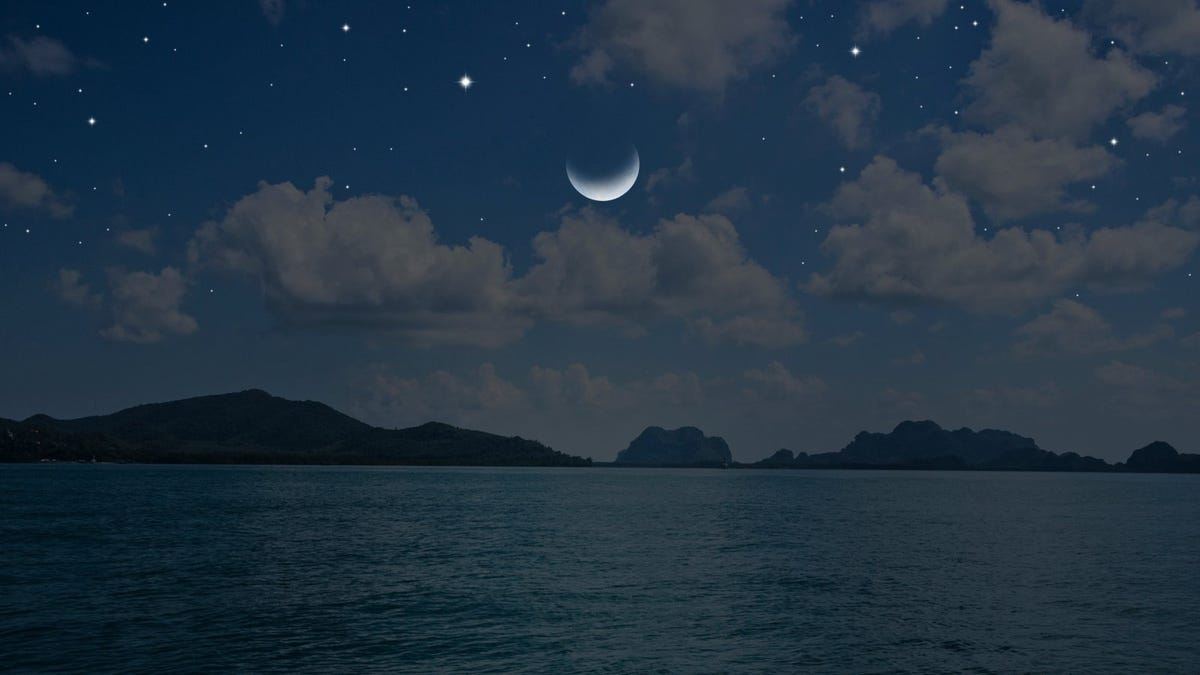 Waning moon and bright stars over blue sea