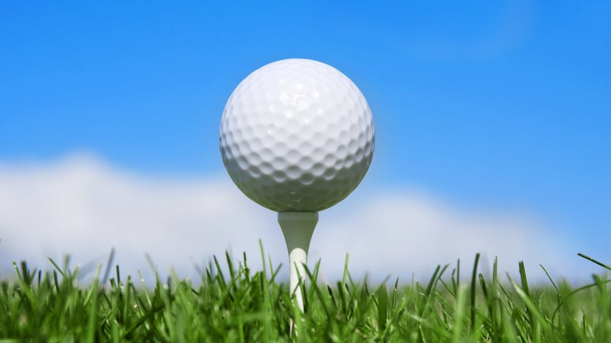 closeup of golf ball on a tee in the grass