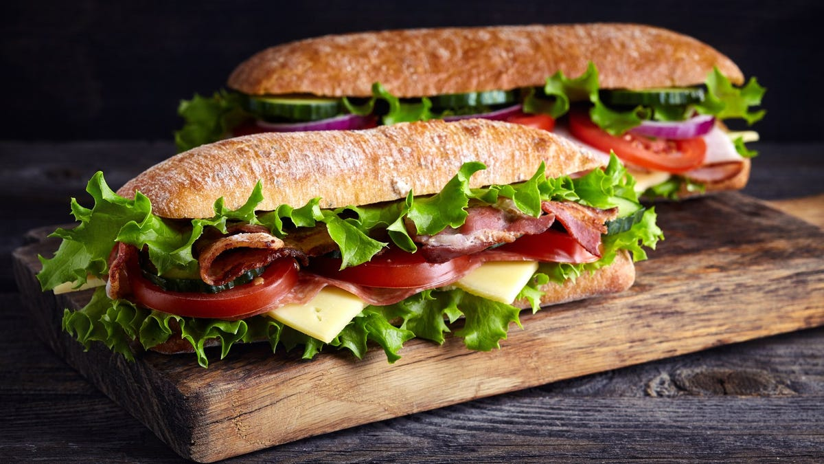 Two fresh sub sandwiches with ham, cheese, bacon, tomatoes, lettuce, cucumbers and onions on wooden cutting board