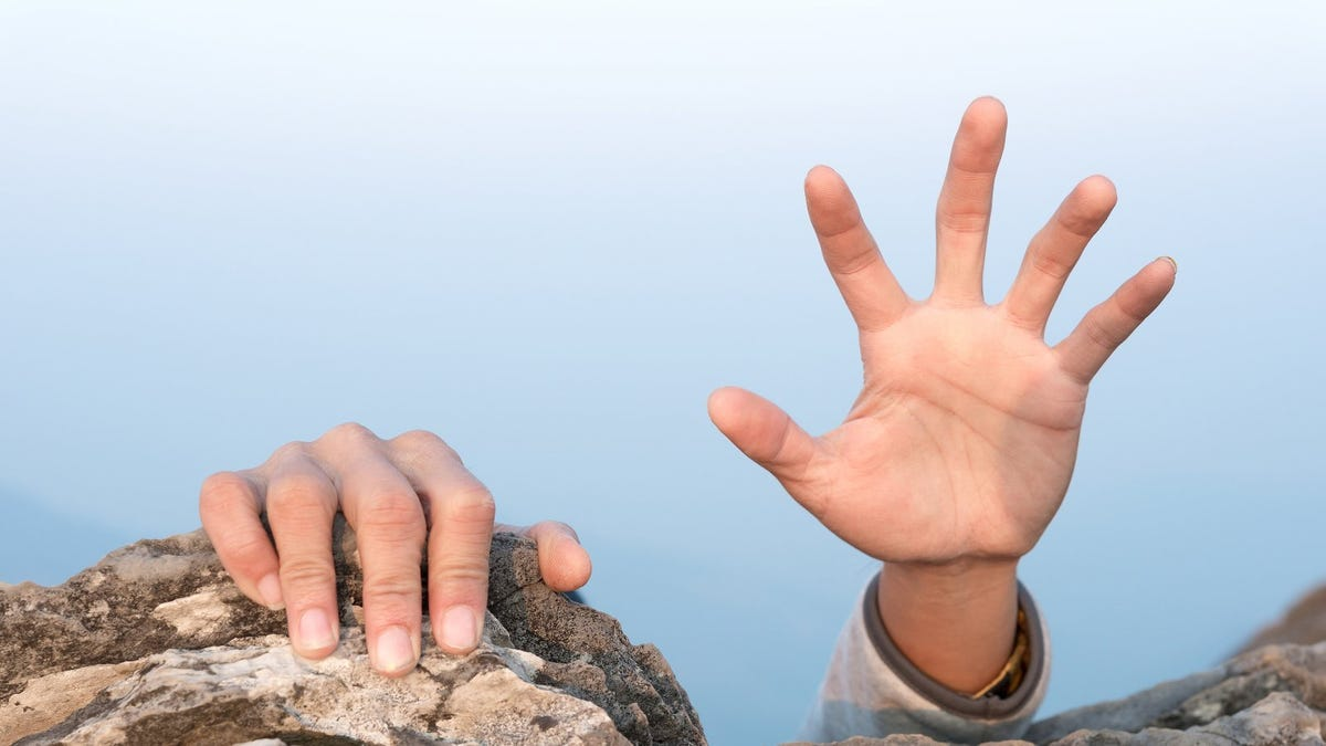 closeup of hands hanging onto cliff